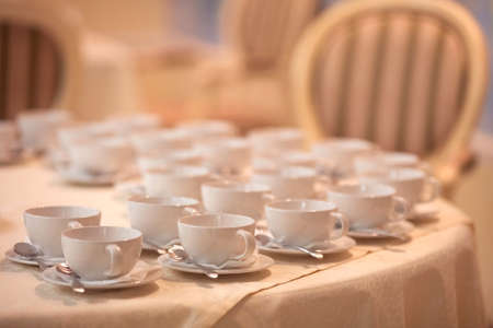 Close-up of stack of white cups for a group of guests.
