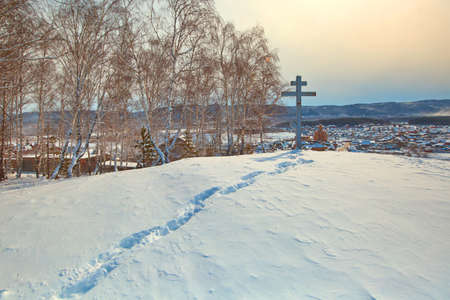 A path in the snow to the memorial cross installed on a mountain in a Russian Orthodox village.