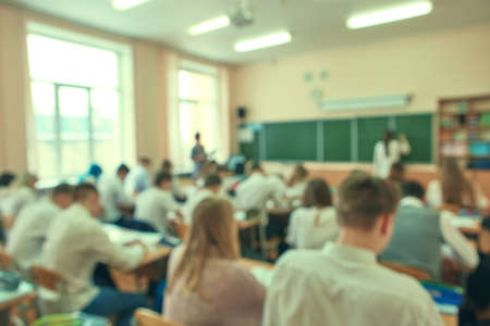 Blurred focus. Abstract background of class room with pupils. 免版税图像