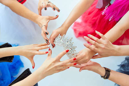 The girls  hands reach for the crown. Who will be the Queen, the boss or the first beauty. The concept of competition and competition.