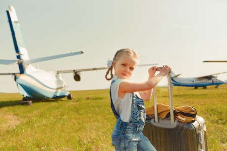 A little girl with a suitcase on the tarmac is going to travel by plane.