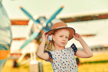A cute child in a romantic hat stands on the tarmac, aircraft propellers in the background. The concept of dreams about traveling