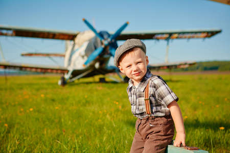 A little boy with a small suitcase on the airfield.