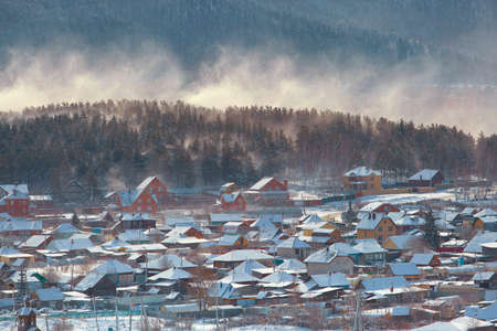 Winter rural landscape with a snowstorm in the Russian Urals with snow covered wooden houses. 免版税图像