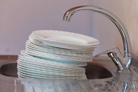 A big pile of dishes in the sink under the water tap 免版税图像