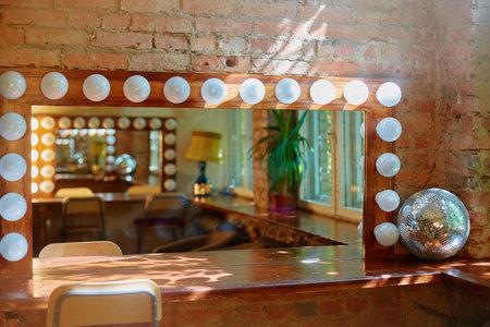 A makeup mirror with light bulbs on a brick wall background 免版税图像
