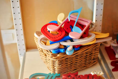 Accessories and props for a photo shoot. In the basket is a pile of colorful plywood figures, letters and symbols.