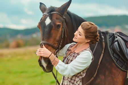 Beautiful elegant female rider next to the horses muzzle. People and animals. Rider. 免版税图像