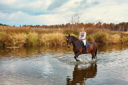 A beautiful girl in a riders tracksuit is sitting on a horse, they went into the water of the reservoir 免版税图像