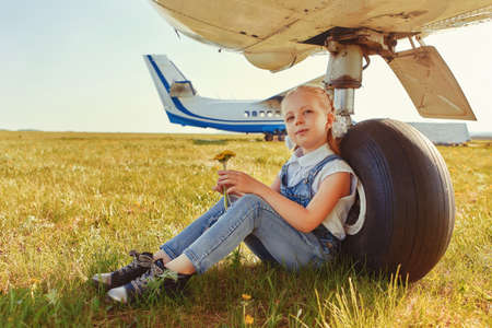 Cute little girl sitting near the landing gear wheels of an airplane and dreaming about traveling and flying in an airplane