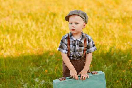 A pretty little child with a suitcase on the field is ready to travel