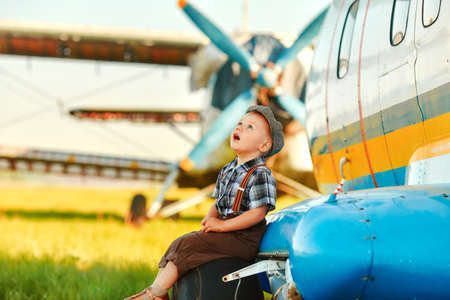 A small child sits on the landing gear wheel of an airplane and dreamily looks at the sky. 免版税图像
