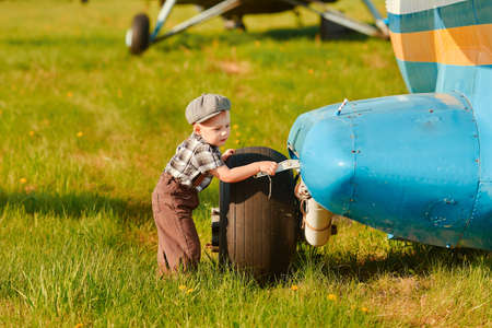 A little boy is curious about the design of the plane. The concept of choosing a future profession 免版税图像