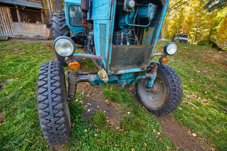An old blue tractor stands in a farmyard 免版税图像