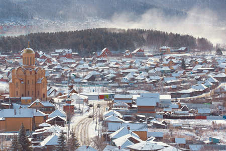 Russian Village in winter. Mountain view of a typical Russian village covered in snow 免版税图像