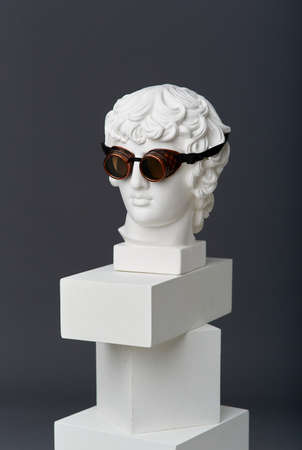 Plaster head of Antinous with round glasses. The concept of the absurd and the combination of the incongruous 免版税图像