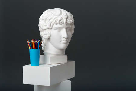 Antinous  plaster head stands next to a set of pencils in a glass. Concept of drawing and creative activities