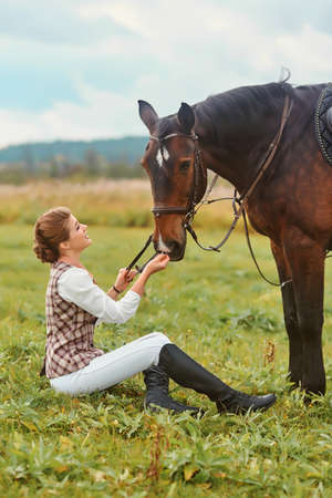 Girl sitting on the grass and stroking her horse