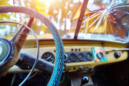 Vintage interior of an old car with a retro dashboard and steering wheel in a PVC cover