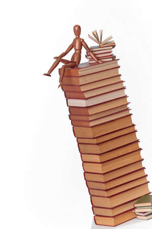 A wooden man sits on a stack of books. Scientific research. The concept is to search for information in books.