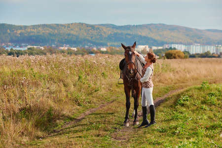 Portrait of a beautiful girl in a classic tracksuit rider with her horse