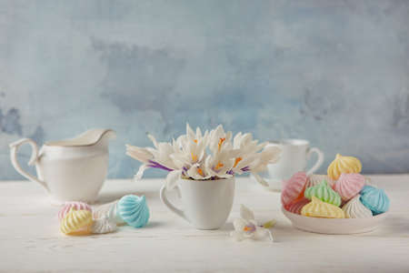 Romantic Breakfast with a Cup of tea, Crocus flowers and sweet multi-colored meringue on the wooden table. 免版税图像