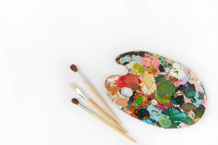 Artists palette and brushes with different colors isolated on a white background