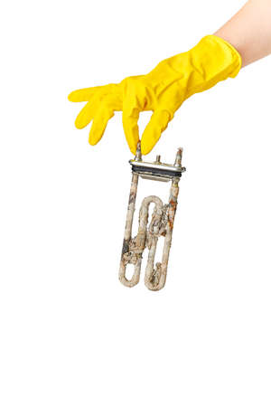 A hand in a yellow glove holds the heating element of a washing machine or dishwasher, covered with a lime coating. The concept of replacement, repair or disposal.
