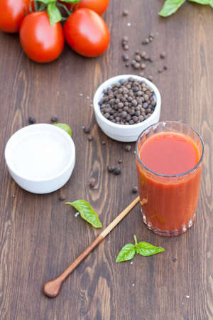 tomato juice: Tomato juice tomatos herbs and spices on wooden table Stock Photo