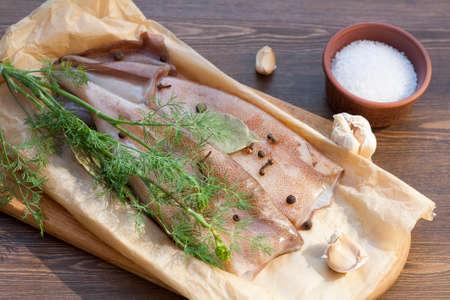 carcass: Verse pijlinktvis karkas met kruiden op papier op de houten tafel, selectieve aandacht Stockfoto