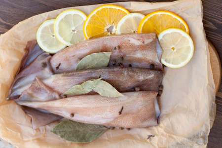 karkas: Fresh squid carcass with spices, lemon and orange on paper, selective focus Stockfoto