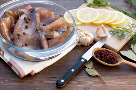 karkas: Fresh squid carcass in a glass pot with herbs and sliced lemon, selective focus