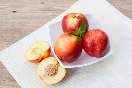 Juicy nectarines in a white plate on the table and slice and nectarines, selective focus