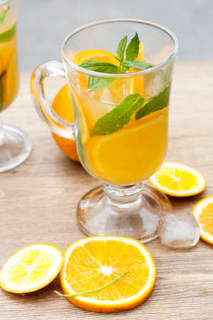 citrous: Orange fresh drinks with ice and mint on wooden table