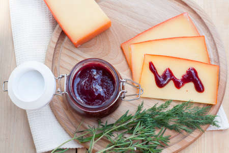 tabla de quesos: Sliced cheese and cherry sauce on a wooden board with dill and rosemary
