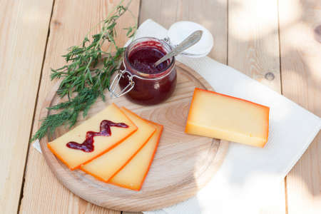 appetising: Sliced cheese and cherry sauce on a wooden board with dill and rosemary