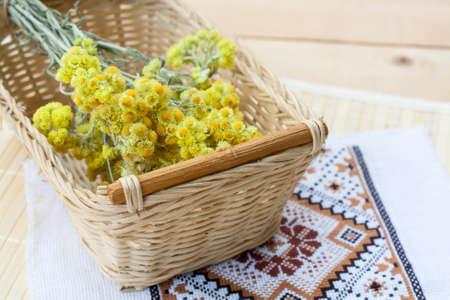 籐のバスケットとライトの木製テーブル、選択と集中の刺繍ナプキンでドワーフ エバーラスト花ブーケ