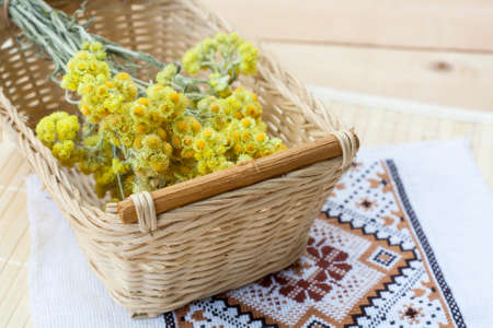 Dwarf everlast flowers bouquet in a wicker basket and napkin with embroidery on light wooden table, selective focus Standard-Bild