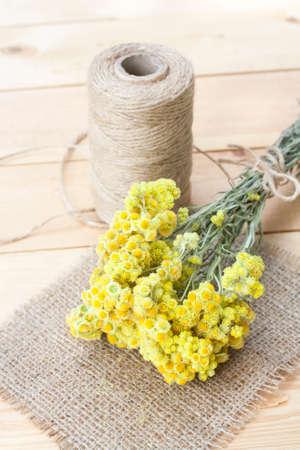 flores secas: Dwarf everlast flowers bouquet, napkin and twine bobbin on light wooden table, selective focus Foto de archivo