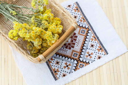 basket embroidery: Dwarf everlast flowers bouquet in a wicker basket and napkin with embroidery on light wooden table, selective focus Stock Photo