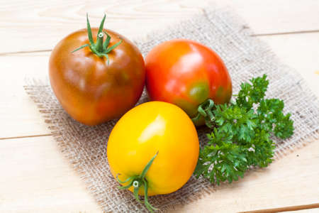 pink black: Assorted tomatoes: orange, pink, black tomatoes with parsle Stock Photo