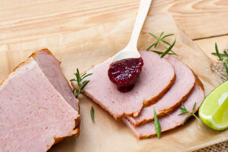 confiture: Smoked meat, rosemary, home made organic cherry confiture and lime on a wooden table Stock Photo