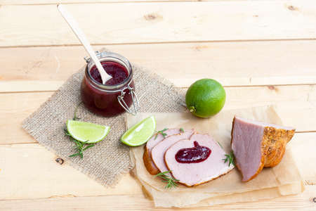 confiture: Home made organic cherry jam confiture, smoked meat, rosemary and lime on a wooden table