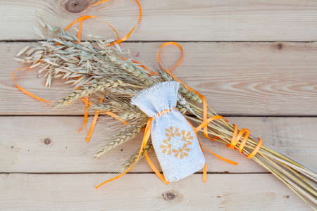 sachet: Sachet with ukrainian embroidery, wheat and oat on wooden background