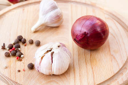cebolla roja: Red onion and garlic bulbs on wooden board close-up, selective focus Foto de archivo