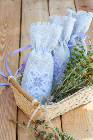 sachet: Sachet with ukrainian embroidery, sheaf of wheat and dried herbs on wooden background