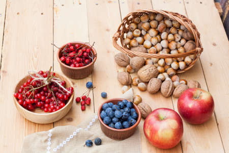 guelder rose berry: Autumn still life with walnuts and hazelnuts in the basket and autumn berry and vegetables on old wooden background, closeup