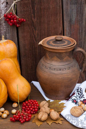 guelder rose berry: Autumn still life in Ukrainian style clay pot and autumn berry and vegetables on old wooden background, closeup