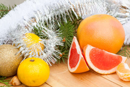 midst: Ripe Cut Red Grapefruit with New Years and Christmas decoration midst fruits and tinsel