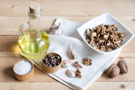 limon: Food ingredients. Oil, eggs, garlic, limon and walnuts on wooden table. Wooden board and napkin. Stock Photo